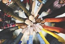 Image of people with hands extended together in a circle, representing teamwork.